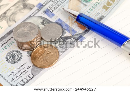 US coins and banknotes with pen on a notebook - stock photo