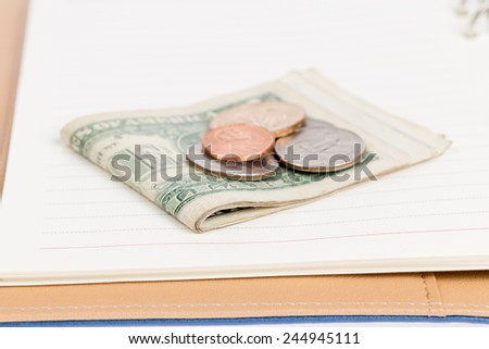 US coins on an empty notebook page - stock photo