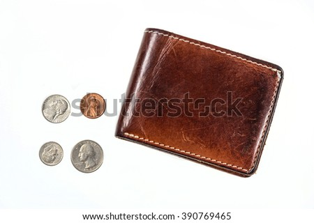US coins spilling out of open leather wallet - stock photo