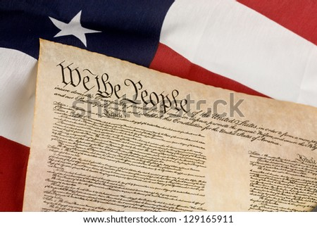 US Constitution against an american flag.