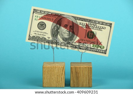 US crisis, decline of American dollar, one hundred US dollars banknote with red arrow down on wooden metal holders over blue - stock photo
