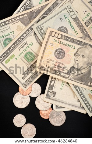 US Currency and Coins on Black - stock photo