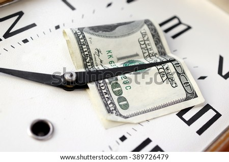 US currency banknote under a minute clock hand, closeup shot, concept of time is money - stock photo