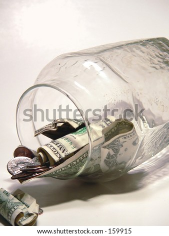 US currency tumbling out of glass jar on neutral background. Vertical image. Concept of having to break into a savings account, could be due to economic recession or downgrade or the last of the money - stock photo