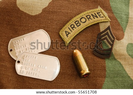 US dog tags, airborne patch, rank and .45 caliber catridge on woodland camo background - stock photo