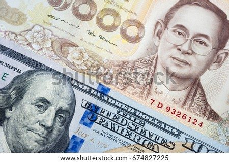 US Dollar and Thai baht banknote background in concept of money exchange, currency trading, business and relationship between America and Thailand.