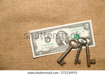 US dollar banknotes and old keys on an old cloth - stock photo