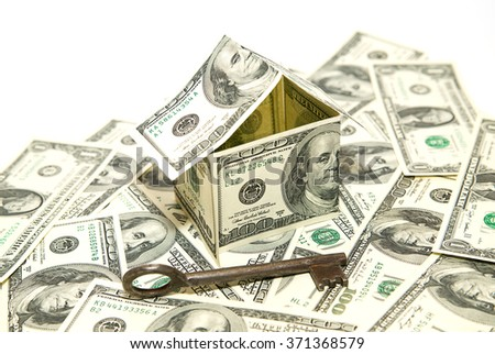US dollar banknotes on display in the shape of a house on white