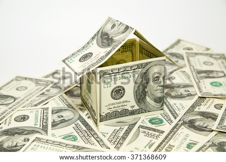 US dollar banknotes on display in the shape of a house on white - stock photo