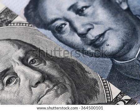 US dollar bill (Ben Franklin) and Chinese yuan banknote (Mao Zedong) close up macro, united states and China money closeup - stock photo
