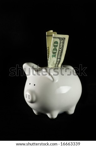 US $100 dollar bill, folded, sticking out of small white piggy bank isolated on black background