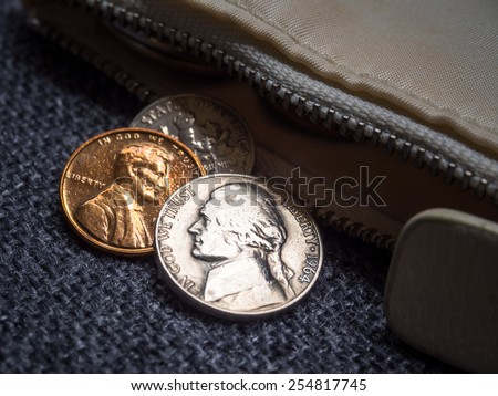 US dollar coins placed outside the wallet. - stock photo