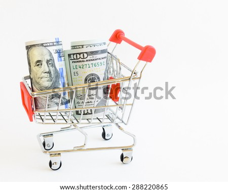 US dollars banknote and coins with shopping cart isolated on white background. Concept of currency, business, finance and online shopping/e-commerce.