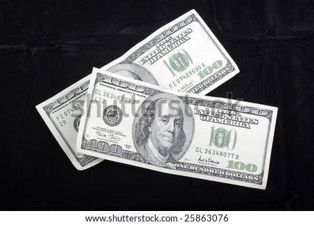 US Dollars banknotes isolated on black velvet background. - stock photo