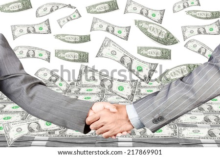 US dollars falling from above into stack of dollars with business handshake at meeting partnership concept  - stock photo
