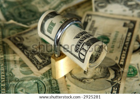 US dollars secured with a padlock on an out-of-focus dollar background - stock photo