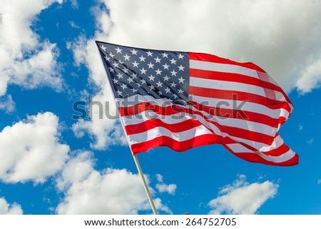 US flag and cumulus clouds behind it - stock photo