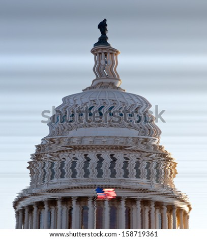 US flag flies in front of the US Capitol in Washington DC in submerged distorted view of the dome of Congress building - stock photo