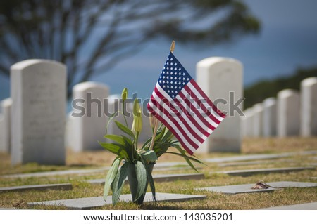 US Flag Flies over military cemetery - stock photo