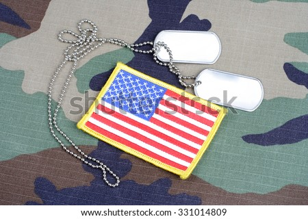 US flag patch with dog tags on woodland camouflage uniform - stock photo