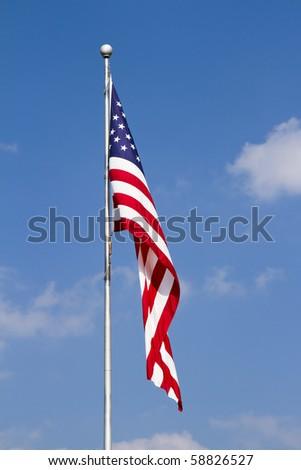 US Flag  waving on Pole against a blue, cloud-draped sky. Vertical. - stock photo