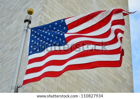 US flag waving with Washington Monument background in Washington DC - United States