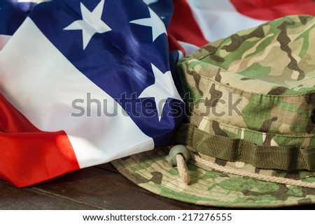 US flag with camouflage cap combat hat - stock photo