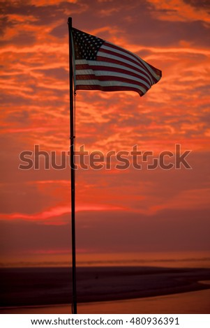 "US Flag with dramatic ""Fire Sky"" sunrise in the background"