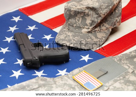 US flag with handgun and US army uniform over it - stock photo