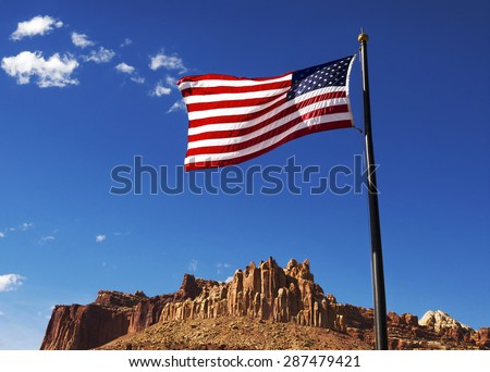 US flag with sandstone rock formations, The Castle, Capitol Reef National Park, Utah, USA - stock photo