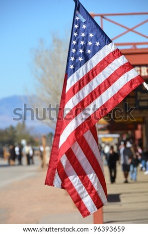 US flag with street scene in the background - stock photo