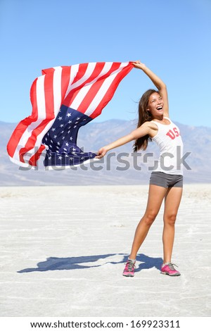 US flag - woman athlete showing american flag. USA sport athlete winner cheering waving stars and stripes outdoors in desert nature. Beautiful cheering happy young multicultural girl joyful excited. - stock photo