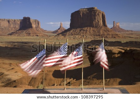 US Flags blowing in wind in front of red buttes and colorful spires of Monument Valley Navajo Tribal Park, Southern Utah - stock photo