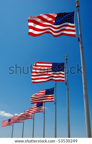 US flags flapping in wind at Washington Monument, Washington DC - stock photo