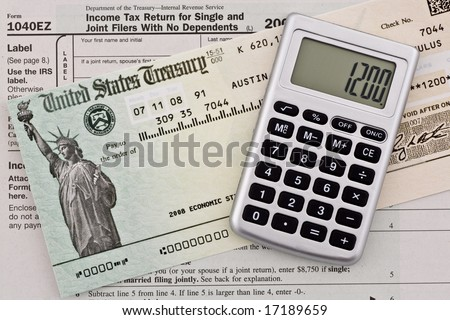US government stimulus refund check with calculator and tax form 1040ez. Numbers have been altered and name removed. - stock photo
