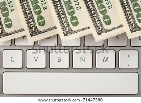 US hundred dollar bills on white computer keyboard with spacebar. - stock photo