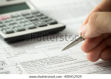 US individual income tax return form with pen and calculator - stock photo