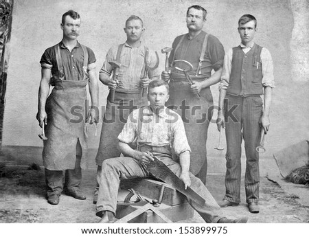 US - KANSAS - CIRCA 1885 - A vintage photo of a group of four young blacksmith's and one carpenter. They are holding the tools used by blacksmiths and carpenters. Photo from Victorian era. CIRCA 1885 - stock photo