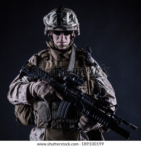 US marine with his assault rifle on black background - stock photo