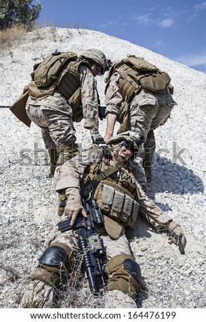 US marines evacuate the injured fellow in arms in the mountains - stock photo