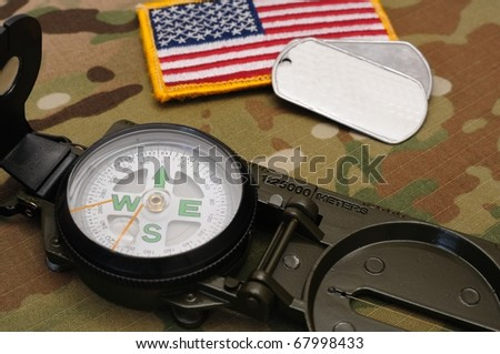 US military compass and US flag patch and dog tags on multicam camo background - stock photo