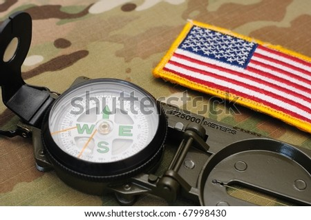 US military compass and US flag patch on multicam camo background - stock photo