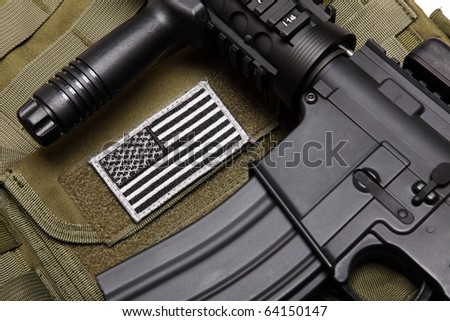 US military concept. Tactical vest with U.S. battle flag and assault rifle with tactical grip close-up. Studio shot. - stock photo