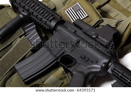 US military concept. Tactical vest with U.S. flag and M4 RIS assault carbine close-up. Studio shot. - stock photo