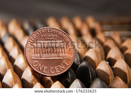 US one cent coin on an old abacus. - stock photo