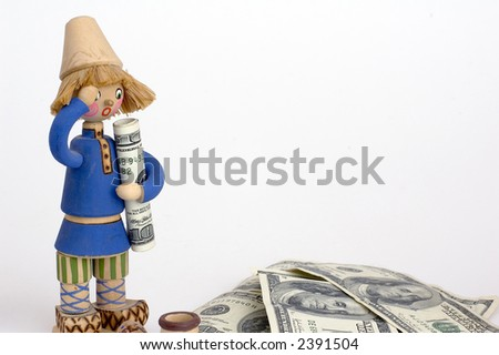 US one hundred dollar bill rolled up in the arms of a small wooden doll,stack of bills on bottom right room for copy on right side - stock photo