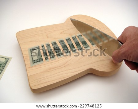 US One Hundred Dollar Note Chopped Into Small Slices Upon A Bread Shaped Cutting Board Under Chef's Knife Held In Right Hand And Another US Hundred Ready On A White Surface With Slight Vignetting. - stock photo