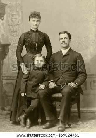 US - OREG0N - CIRCA 1885 - A vintage antique photo of a family of three. The mother is standing behind her young son with the father sitting in a chair. A photo is from the Victorian era. CIRCA 1885 - stock photo