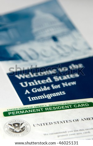 US permanent resident card (Green Card) seen with welcome to the USA brochure - stock photo