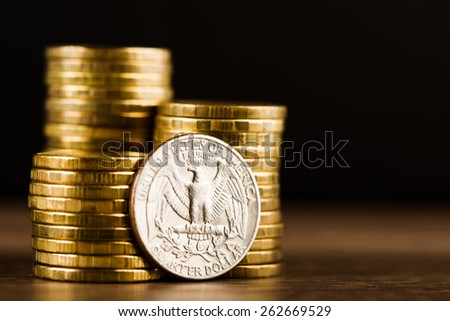 us quarter dollar coin and gold money on the desk - stock photo